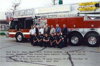 A group of firefighters together in front of fire trucks.