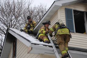 3 firefighters on a roof.